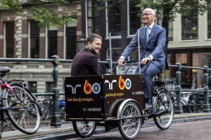 Randstad 2020: CEO Jacques van den Broek geeft Niek Karsmakers een lift op de bakfiets