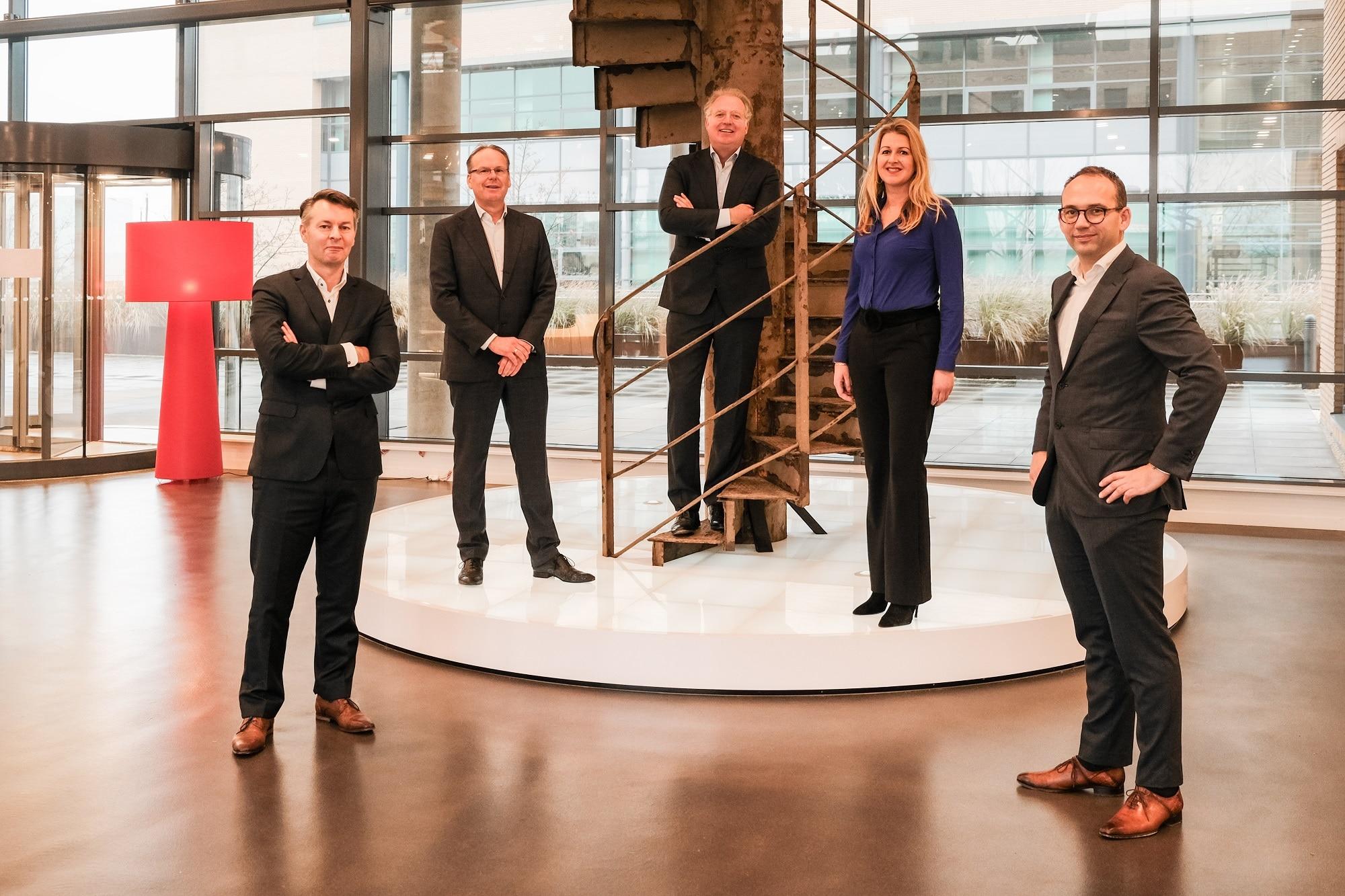 """V.l.n.r.: Thomas Meijer (Algemeen Directeur Palladio), Albert Kraak (oprichter Palladio), Gert-Jan Meppelink (CEO EIFFEL), Karima van Zadelhoff-Charrat (Directeur People & Organisation EIFFEL) en Bram van Beetz (Commercieel Directeur EIFFEL) in de hal van EIFFEL bij een origineel trapdeel van de Eiffeltoren: """"We zetten nieuwe stappen omhoog""""."""